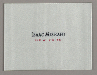 Isaac Mizrahi, in black Bodoni capitals, is centered. The M has been altered so as to appear splayed, or awkwardly spread out. New York, in smaller red capitals, is on one line directly underneath.