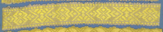 Yellow trimming fragment in a design of ornamental motifs within lozenge shapes; picot edges.
