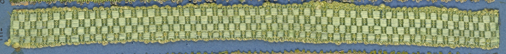 Green and tan trimming fragment in a checkerboard design.
