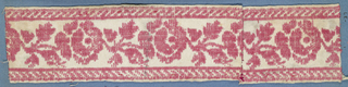 Red and white trimming fragment in a design of roses with buds and leaves set between borders of diagonal lines.