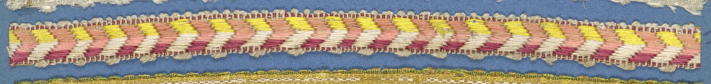 Trimming fragment in a design of chevrons in shades of red alternating with chevrons of yellow and white; picot edges.