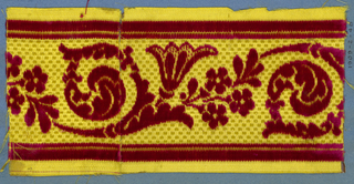 Trimming fragment in a design of flowers sprays and scrolling leaves in red cut velvet on a yellow checkerboard ground.
