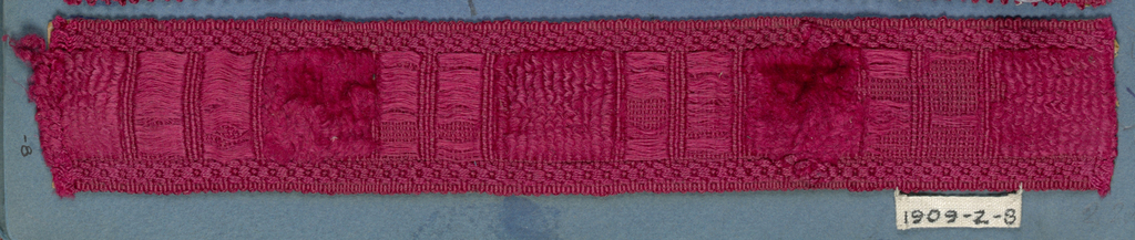 Red trimming fragment in a design of single wide blocks separated by two narrower blocks.