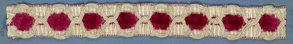 Red and white trimming fragment ornamented with white cord (gimp) arranged to form a pattern of interlocking compartments.