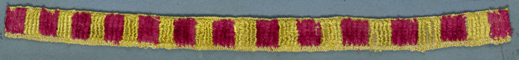 Trimming fragment in a design of red and yellow blocks in cut and uncut velvet.
