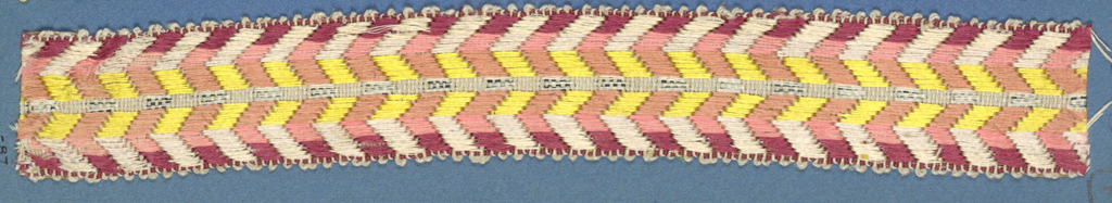Trimming fragment in a design of chevrons in shades of red alternating with chevrons in yellow and white.