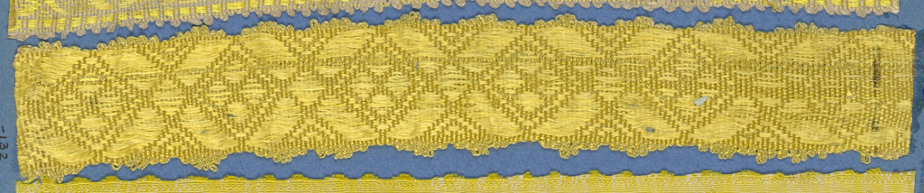Yellow trimming fragment in a design of decorated lozenge shapes; scalloped edges.
