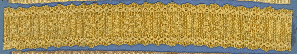 Yellow trimming fragment in a design of a central band with flower ornaments separated by lines and between chain borders; picot edges.
