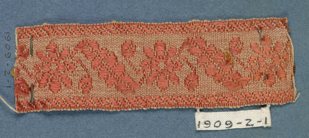 Dark orange trimming fragment in a design of open flowers and diagonally placed leaves between borders in twill pattern.