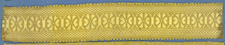 Yellow trimming fragment in a design of eight-petal flowers alternating with linear motifs; checkerboard borders and picot edges.