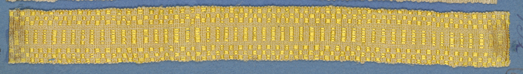 Yellow trimming fragment in a design of a central band of stripes between checkerboard borders.