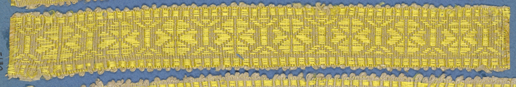 Yellow trimming fragment in a design of four-petal flowers separated by linear motifs; picot edges.