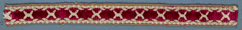 Red and white trimming fragment ornamented with white threads arranged to form a pattern of interlocking compartments.
