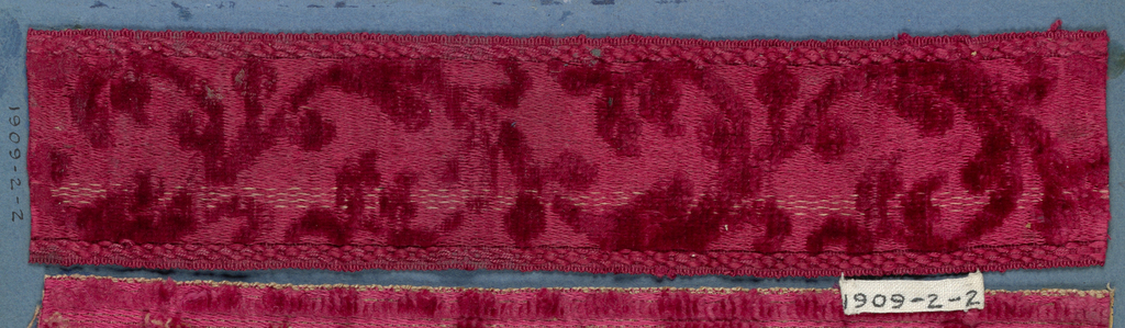 Red trimming fragment in a design of scrolling leaves.