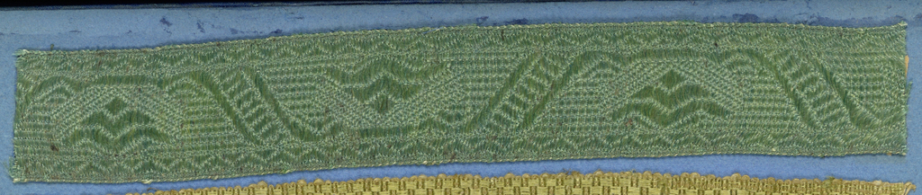 Green trimming fragment in a design of triangular shapes within diagonal bands and chevron borders.