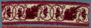 Trimming fragment in a design of flowers, leaves and tendrils on scrolling stems in red on a white satin ground with an appliqué of red cord. Narrow red cord (gimp) on both edges.