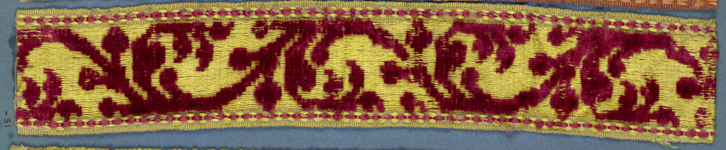Trimming fragment in a design of an angular stem with leaves in red cut velvet on a yellow satin ground.