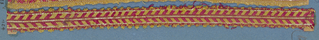 Trimming fragment in a design of red and yellow diagonal lines arranged to form chevrons; picot edges.