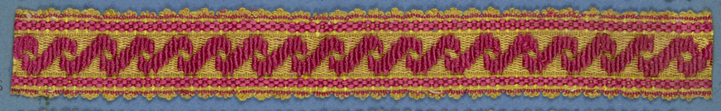 Trimming fragment in a design of crossing ribbons in red on a yellow ground with red stripes; picot edges.