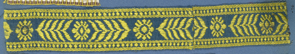 Yellow and blue trimming fragment in a design of an open flower with chevron-like leaves at either side.