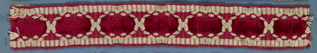 Red and white trimming fragment ornamented with white threads arranged to form pattern of interlocking compartments.