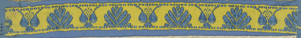 Blue and yellow trimming fragment with a leaf design and conventional forms.