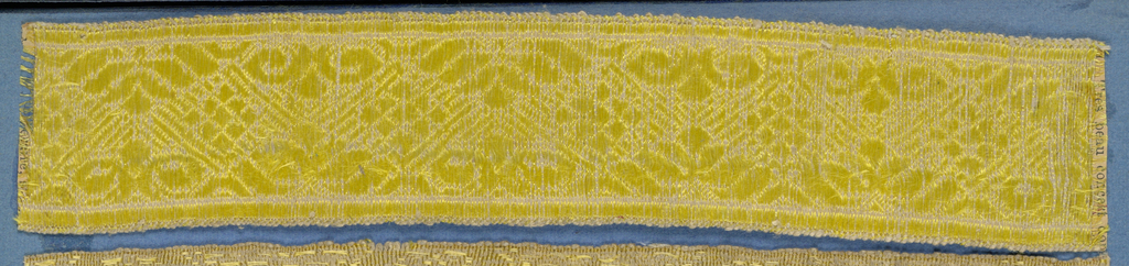 Yellow trimming fragment in a design of ornamented lozenges with scrolls and leaf forms.