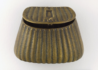 In the form of a fishing basket, with raised, simulated woven straw on canted lid and body, small loop of twisted straw at front of lid, longer twisted loop at basket back, some green patination in crevices. Flat lid hinged on back. Incised lines on bottom serve as striker.
