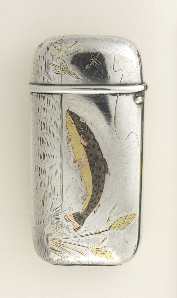 Oblong, curved sides and corners; one side featuring incised and inlaid decoration of trout leaping out of water, situated horizontally on box body,  its back a dark, oxidized color, its underside brass, fins and eyes copper, stalk-like vegetation on right, some vegetation on left, fishing line with fly attached suspended in air on upper left; reverse features fisherman, situated vertically on box, with fishing rod line caught in seat of his pants, he wears dark, oxidized jacket and shoes, brass colored hat and shirt, copper colored pants, grassy bank brass color, with brass tipped cattails on right and left. Lid hinged on side. Striker on bottom.