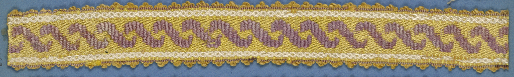 Trimming fragment in a design of crossing ribbons in lavender on a yellow ground with white stripes; picot edges.