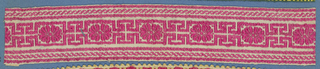 Red and white trimming fragment in a design of a fret pattern with open flowers between borders of twisted bands.