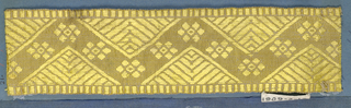 Yellow trimming fragment in a zigzag design with open flowers. Triangular spaces filled with lines meeting at right angles.