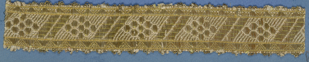 Yellow trimming fragment in a design of open flowers and diagonal lines set between sawtooth borders; gilt picots.