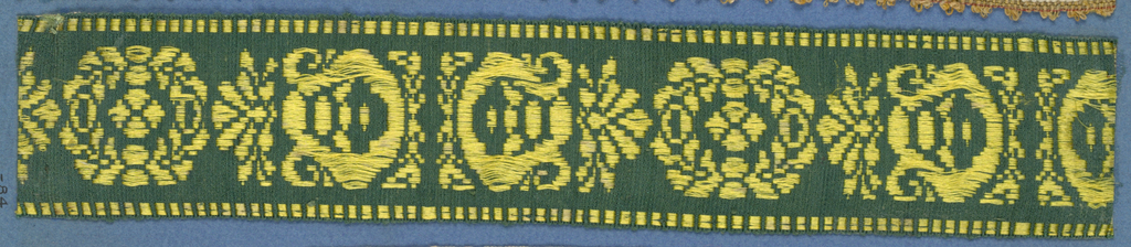 Trimming fragment in a design of alternating ornaments comprised of leaves, scrolls and dots in yellow on a green ground.