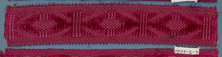 Red trimming fragment in a design of ovals separated by bars and with a picot edge.