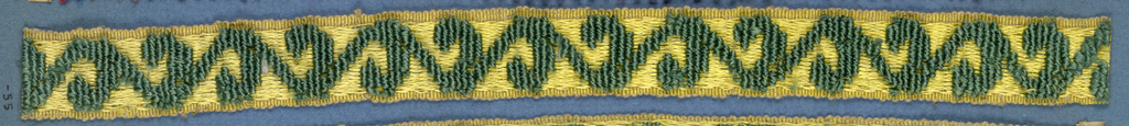 Green and yellow trimming fragment in a design of a serpentine stem with leaves.