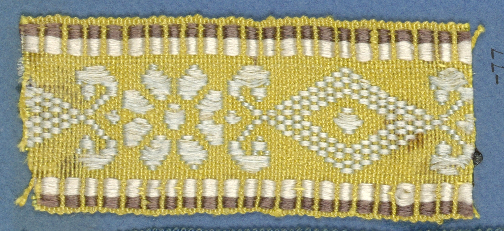 Yellow, white and brown trimming fragment in a design of an open flower alternating with lozenges decorated in scroll pattern.