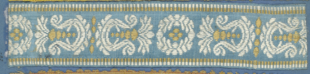 Trimming fragment in a design of alternating ornaments comprised of leaves, scrolls and dots in white and yellow on a blue ground.