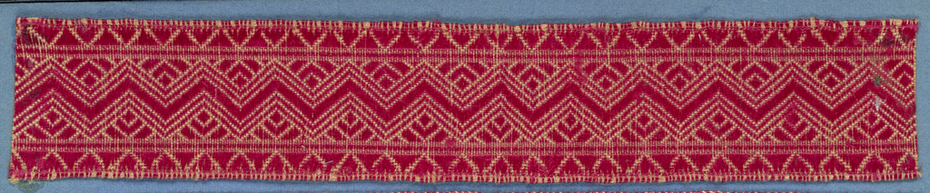 Red trimming fragment in a design of a conventionalized flower placed alternately up and down and separated by chevron bands; border in pattern of triangles.