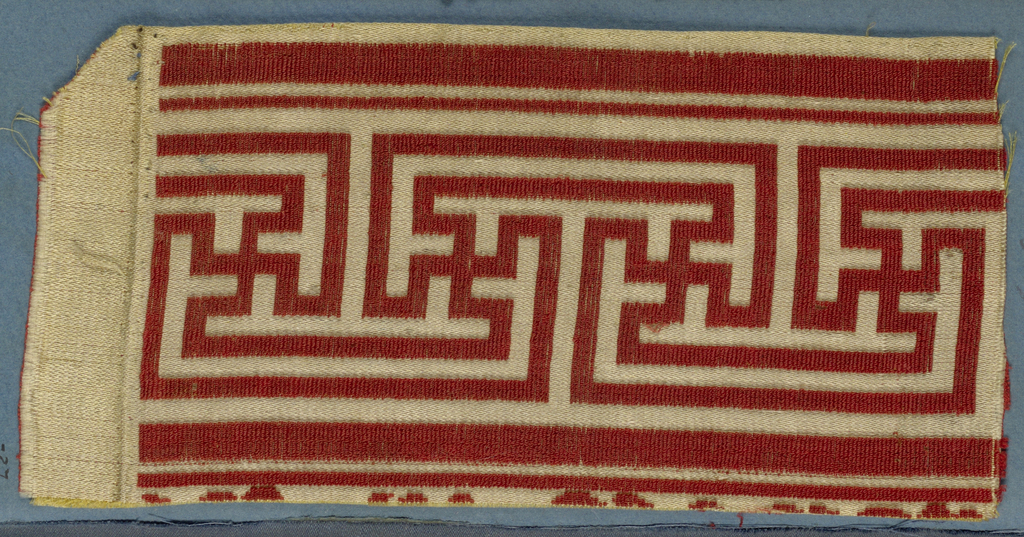 Trimming fragment in a design of red fretwork on a yellow ground.