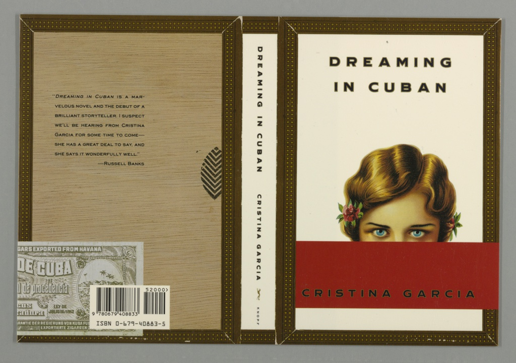 Book jacket for Dreaming in Cuban, by Cristina Garcia, published by Alfred A. Knopf. Front and back cover are depicted as sides of a cigar box, with square patterned border on edges and wood grain pattern with cigar label on back. On front cover, a woman with flowers in her hair and blue eyes, mouth covered by red rectangle at bottom. Text above, in black: DREAMING IN CUBAN; below, in black on red rectangle: CRISTINA GARCIA.