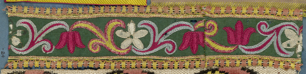 Trimming fragment in a design of tulips and five-petal flowers with leaves worked in chain stitch in red, yellow, white and blue on a green ground. Narrow lace edging on both sides in pink and yellow.