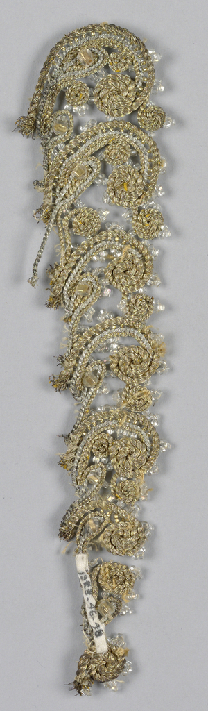 Gold and silver metal cord in scroll design, graduating large to small from left to right. Glass beads on edge of scrolls.
