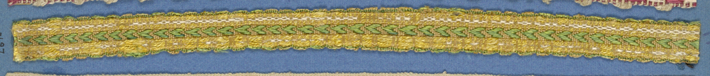 Trimming fragment in a design of green chevrons between borders of yellow and white.