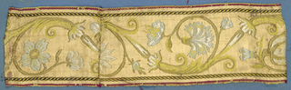 Blue, white, yellow, green and gold trimming fragment in an incomplete design showing flowers, leaves and scrolls.