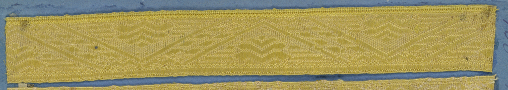 Yellow trimming fragment in a design of diagonal lines forming triangles with conventionalized leaf ornaments inside.