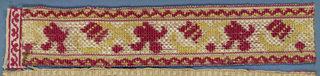 Trimming fragment in a design of flower spray with scrolling stem in red and yellow on a white ground. Borders showing scallops in red and yellow.