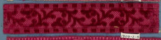 Red silk trimming fragment in a design of leaves on an angular stem.