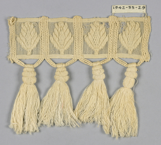 Header of gauze weave separated into four rectangles, each with an upright leaf inside. Rectangles are formed by thicker threads which are carried down to create loops underneath that support large tassels.
