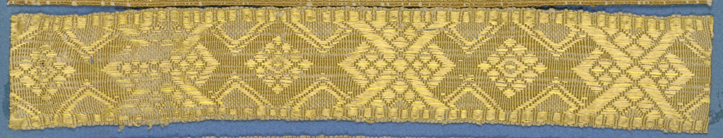 Yellow trimming fragment in a geometic design based on lozenge forms.